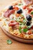 Pizza with smoked ham and cherry tomatoes