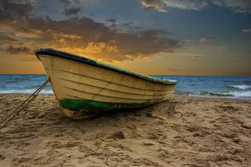 Fischerboot am Strand mit Sonnenuntergang