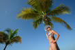 Woman in summer hat sunbathing under a palm tree on a background