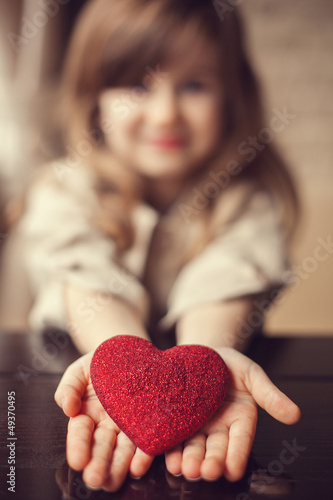 Valentine's Day -  dreaming cute child with red Heart in hands