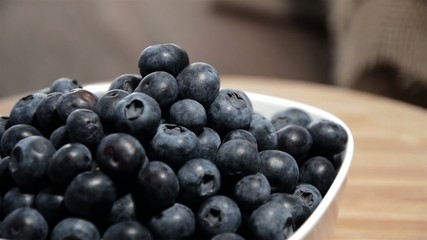 Rotating Blueberries in a bowl on a wooden plate