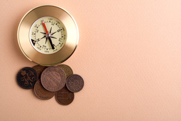 compass with old coins on a brown background