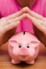 Zwei Hände über einem rosa Sparschwein