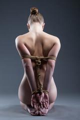 Nude young woman with shibari