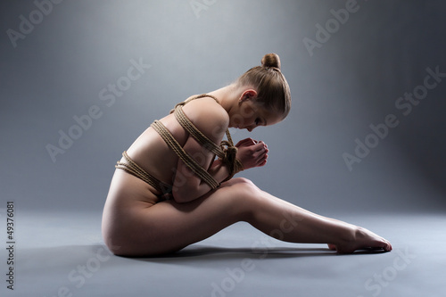 Sexy young woman with shibari sitting on floor