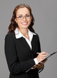 Smiling business woman with clipboard, on gray