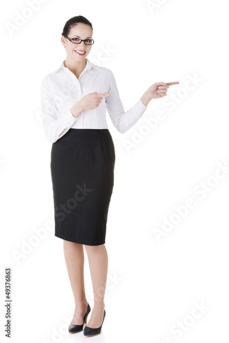 Happy young business woman showing copy space