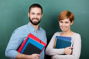 zwei lächelnde studenten mit unterlagen