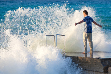 Man on the pier against the big wave