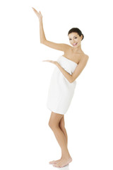 Happy woman in towel showing copy space