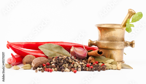 brass mortar and spices isolated on white