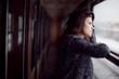 Femme accoudée à une fenêtre dans les couloirs d'un train