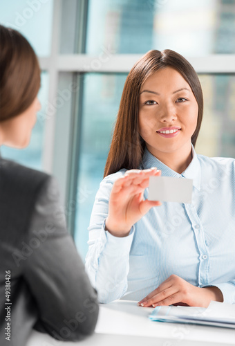 Two successful business women reaching agreement at office and s