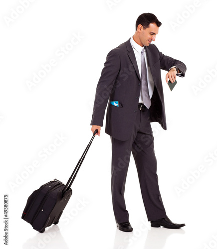 businessman walking with trolley bag and looking at his watch