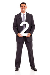young businessman holding number 2 isolated on white