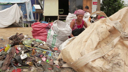 Garbage gatherers assorting trashes in slums