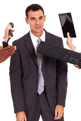 tired male office worker with multiple gadgets around him