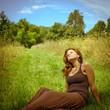 Young brunette woman relaxing in a sunny field