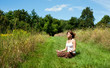 Young woman in lotus position meditating in nature