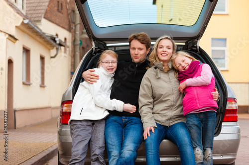 Family on a car trip sitting in the back