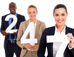 group of business people holding numbers 24 7