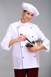 Portrait of young woman chef with pan on grey background