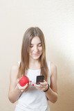 blonde woman holding a red apple cell phone