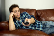 Young man on couch with remote control