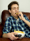Young man on couch eating potato chips