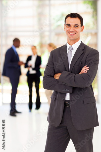 handsome businessman arms folded portrait in office