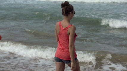 Young happy woman by the sea, super slow motion