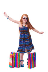 Child shopping. Happy fashion little redhead girl with shopping