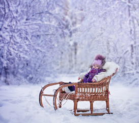 Baby girl portrait in old fashioned sled