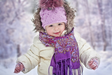 Baby girl's portrait on winter forest background