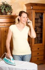 Hausfrau bügelt Wäsche und telefoniert dabei