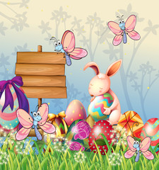 The bunny and the butterflies in the garden with Easter eggs