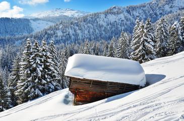 Schräger Stall unter dicker Schneedschicht