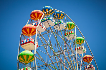 Close-up of colorful ferris wheel on vivid blue sky