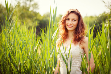 Portrait of beautiful woman in green grass