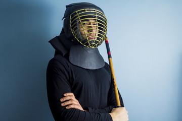 An eskrimador wearing protective helmet