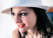 Portrait of sensual smiling woman with white hat seat on a chair