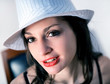 Portrait of pretty smiling woman with white hat seat on a chair