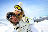 Skier at the mountain giving piggyback ride to girlfriend