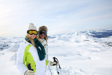 Couple of skiers standing on the top of snowy mountain
