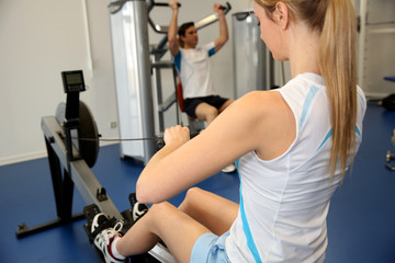 Woman using rowing equipment in gym center