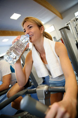 Woman in fitness class drinking water from bottle