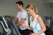 Couple in fitness gym using running belt