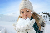 Woman blowing snow flakes towards camera