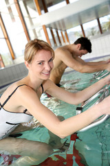 People exercising with aquatic bikes in spa center