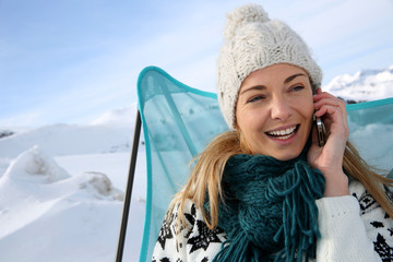 Woman in ski resort using smartphone